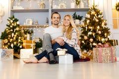 Sweet couple opening Christmas gifts stock photography
