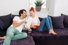 Sweet Couple Resting on Couch While Reading a Book Royalty Free Stock Photo