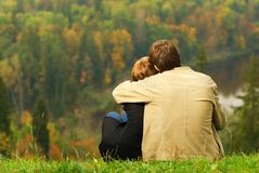 Sweet couple sitting on a hill royalty free stock photo