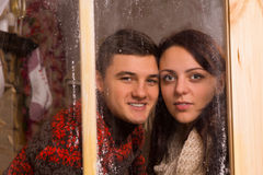 Sweet Couple Smiling Behind Glass Window. Close up Young Sweet Couple Smiling Behind Glass Window with Touching Faces While Looking at the Camera Stock Photography