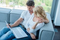 Sweet Couple on Sofa Watching Something at Laptop Stock Images