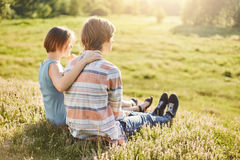 Sweet couple of teenagers sitting outdoors on greenland embracing admiring fresh air and sunlight having talk sitting backs. Cute Royalty Free Stock Photography