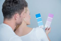 Sweet Couples Looking at Colored Paper Together Royalty Free Stock Photography