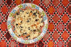 Sweet couscous with almond and dried fruits on red handmade carp Stock Photography