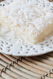 Sweet couscous pudding with coconut on white vintage plate on wo Royalty Free Stock Images
