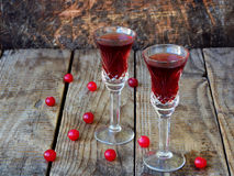 Sweet cranberry alcohol drink liqueur in two glasses and bottle on wooden background. Stock Photography