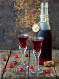 Sweet cranberry alcohol drink liqueur in two glasses and bottle on wooden background. Royalty Free Stock Images