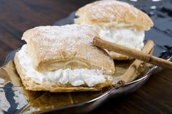 Sweet cream cakes and cinnamon Stock Photos