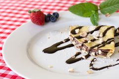Sweet crepe with chocolate and fruit. Sweet crepe with chocolate, strawberries, blueberries and some leaves of mind Stock Photography