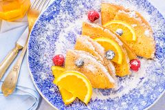Sweet crepes with powdered sugar and berries breakfast plate. Royalty Free Stock Images