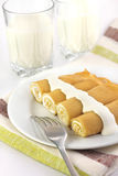 Sweet crepes stuffed with cottage cheese. On white plate royalty free stock photography