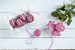 Sweet crimson french macaroons with box and hyacinth on light dyed wooden background Royalty Free Stock Photo