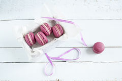 Sweet crimson french macaroons with box on light dyed wooden background Stock Photo