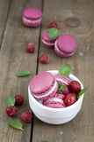 Sweet crimson french macaroons wiht hyacinth flowers and mint on dark wooden background Royalty Free Stock Photo