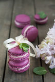 Sweet crimson french macaroons wiht hyacinth flowers and mint on dark wooden background Royalty Free Stock Photos