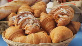 Sweet croissants in a basket on the table. Breakfast background with almond croissants. Delicious fresh croissants stock video footage