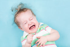 Sweet crying baby on a blue blanket Stock Photo