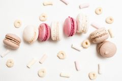 Sweet culinary art of macaroons on white backdrop. Top view. Delicious cakes with corn flakes and marshmallow close up Royalty Free Stock Image
