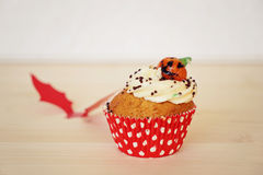 Sweet cupcake decorated with cream and marzipan pumpkin on Halloween Stock Image