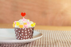 Sweet cupcake on disk with wood background color Stock Photos