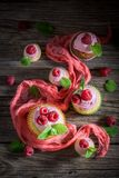Sweet cupcake with fresh raspberries and pink cream. On wooden table Stock Images