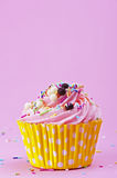 Sweet cupcake with sprinkles and chocolate balls  on a p Royalty Free Stock Photos
