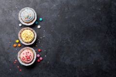 Sweet cupcakes. With colorful decor and candies. Top view with space for your greetings stock images