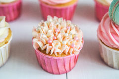 Sweet cupcakes with cream, decorated gingerbread, beads and makarons for gentle refined girl or a little princess Stock Photos