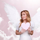 Sweet cupid girl. Closeup portrait of sweet cupid girl with big white wings and heart in hands in pink heaven, happy Valentines day, bring love for people stock photos