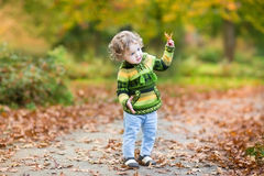 Sweet curly baby girl dancing in autumn park Royalty Free Stock Photo