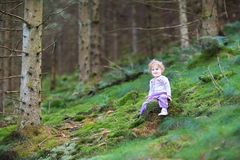 Sweet curly baby girl playing in pine wood forest Stock Images