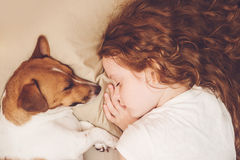 Sweet curly girl and dog is sleeping in night. Royalty Free Stock Photos