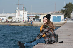 Sweet curly teen sitting on the edge of the port Stock Photography