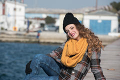 Sweet curly teen sitting on the edge of the port Stock Images