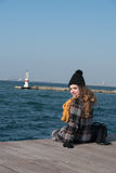 Sweet curly teen sitting on the edge of the port Royalty Free Stock Photos