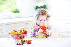 Sweet curly toddler girl having breakfast drinking juice Royalty Free Stock Image