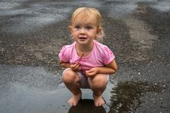 Cute baby girl is standing barefoot in puddle after rain Stock Images