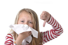 Sweet and cute blond hair little girl blowing her nose with paper tissue having a cold feeling sick. 7 or 8 years old sweet and cute blond hair little girl Stock Images