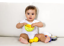 Sweet cute little baby sitting on couch alone at home playing with toys happy and relaxed having fun Royalty Free Stock Photos