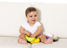 Sweet cute little baby sitting on couch alone at home playing with toys happy and relaxed having fun Stock Image