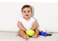 Sweet cute little baby sitting on couch alone at home playing with toys happy and relaxed having fun Royalty Free Stock Image