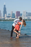 Sweet and dashing teen couple. A young couple in a romantic and sensual mood on a sunny day standing by the riverside. On the background, several highrise Stock Photography