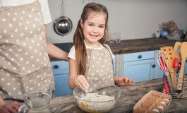 A sweet daughter mixes eggs and flour in a bowl. The girl is going to do the mafina with her mother stock images
