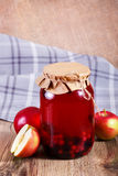 Sweet delicious compote of berries in glass jar on wooden table. Sweet delicious compote of berries and apples in glass jar on wooden table. Summer fruit drinks Royalty Free Stock Images