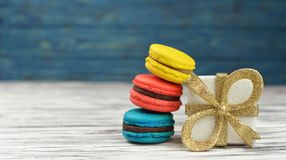 Sweet delicious cookies macarons  with a golden box. Sweet delicious cookies macarons pink, yellow, blue on a wooden background with a golden box for the new Royalty Free Stock Photo