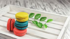 Sweet delicious cookies macarons on a light wooden background. Sweet delicious cookies  macarons red, yellow, blue on a light wooden background in a wooden box Royalty Free Stock Photos