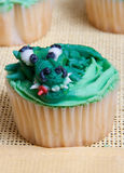 Sweet Delicious Crocodile Character on Cupcake Stock Images
