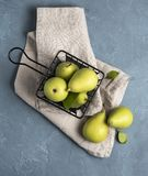 Sweet delicious green  pears inside  black basket on the blue table fruit. Sweet delicious green pears inside black basket on the blue table royalty free stock photos