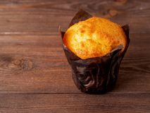 Sweet delicious muffin, on brown wooden background. Sweet delicious muffin, on the brown wooden background Royalty Free Stock Photography