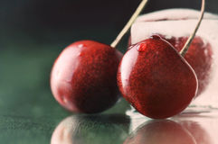 Sweet delicious ripe cherries on green table with water drops ma Stock Image